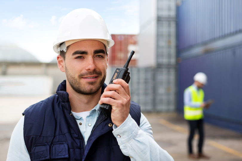 View of a Young Attractive docker using talkie walkie at work