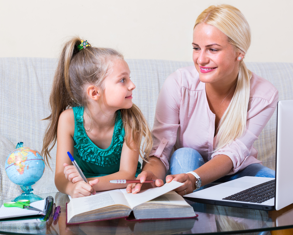 Portrait of smiling young woman and cute little girl having lesson indoors