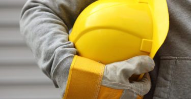 Man holding yellow helmet close up