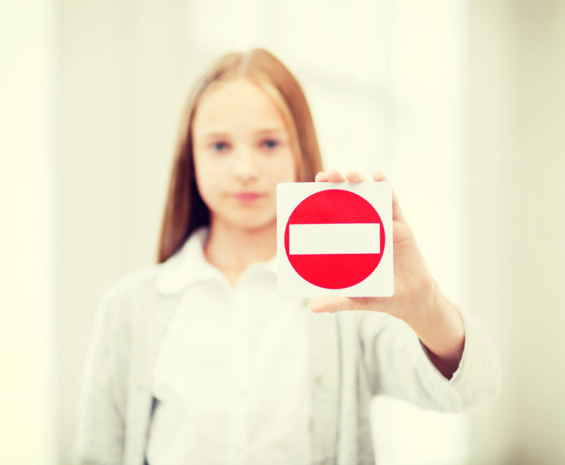 education, school and anti-bullying concept - student girl showing no entry sign