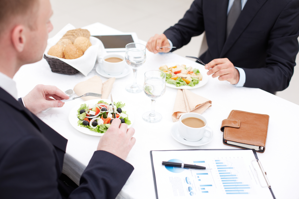 Close-up of businessmen sitting in cafe and having business lunch