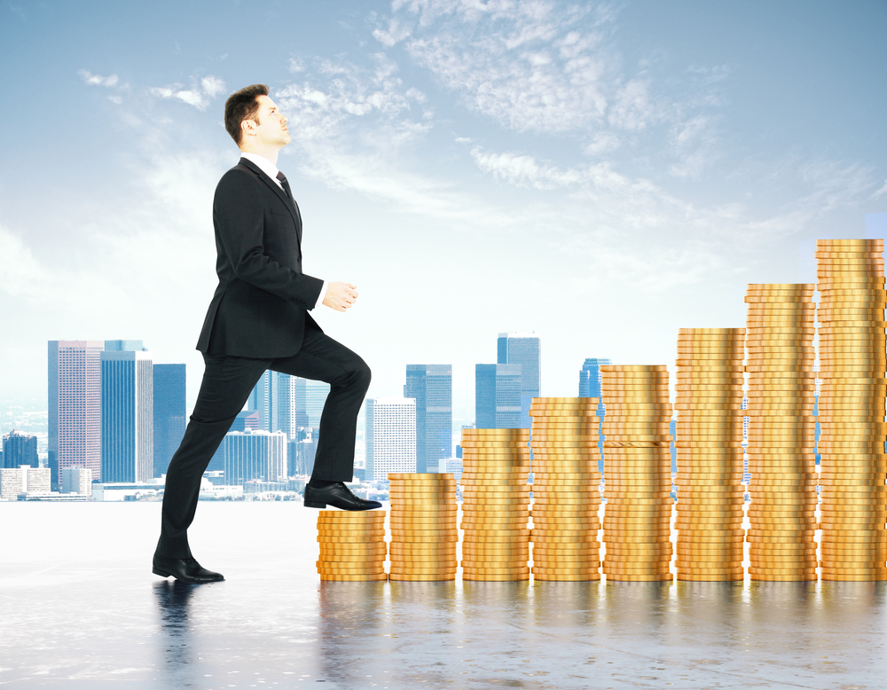 Increase in profits concept with businessman climbs the stairs of gold coins at city background
