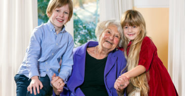 Attractive happy little boy and girl with their grandmother posing with her in the living room as they hold hands and touch heads tenderly while smiling happily at the camera.