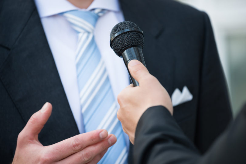 Midsection of male journalist taking interview of businessman outdoors
