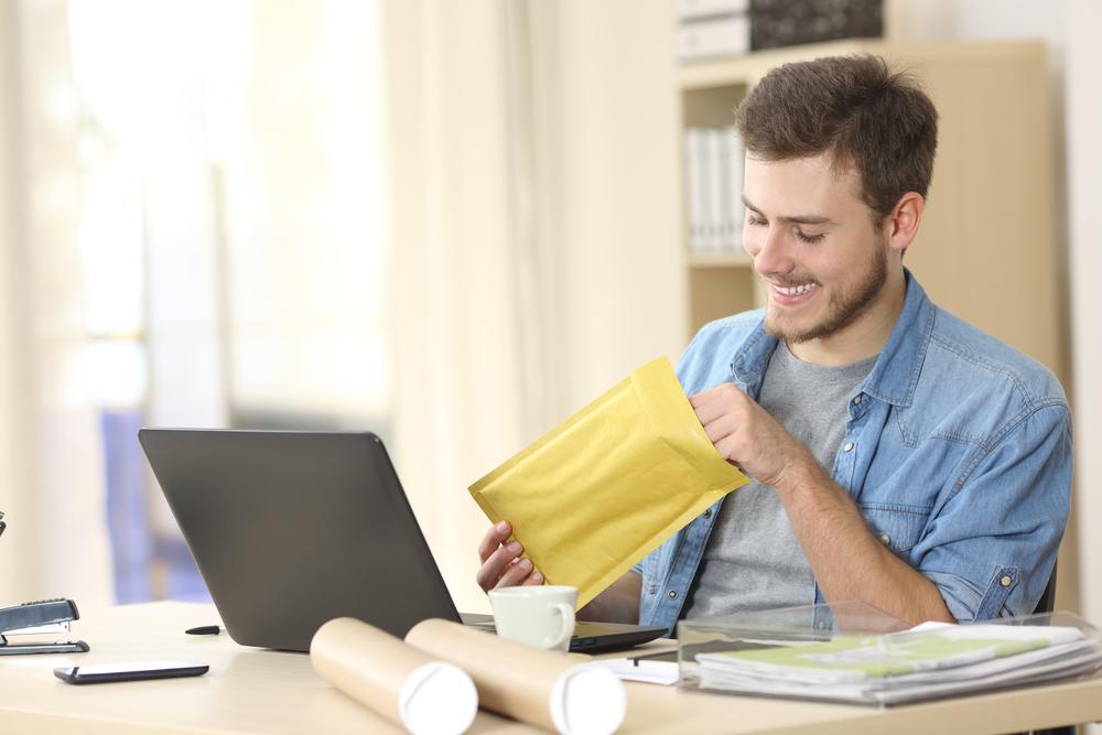 Entrepreneur opening a padded envelope