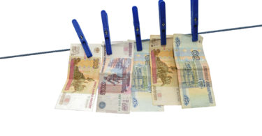 Russian rubles banknotes hanging on laundry line attached with plastic clothespins against white background
