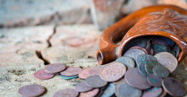 Ancient clay mug full of old coins. The treasure was found in an old building