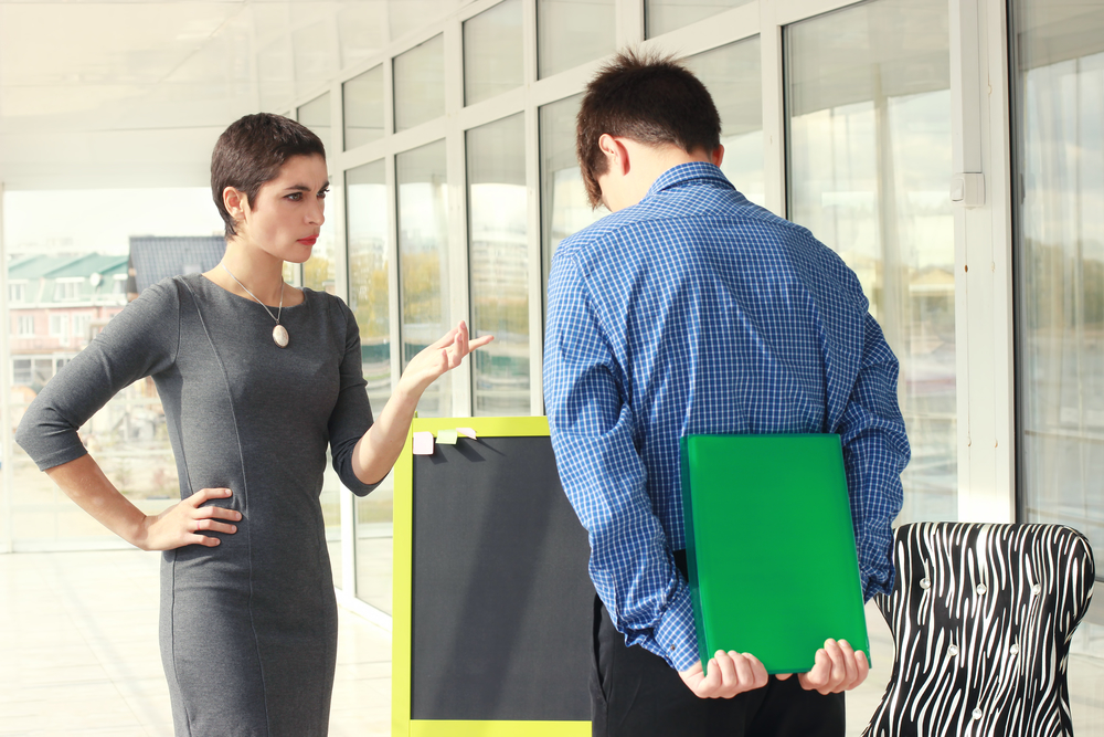 Angry female boss talking to worker male in office. Business wom