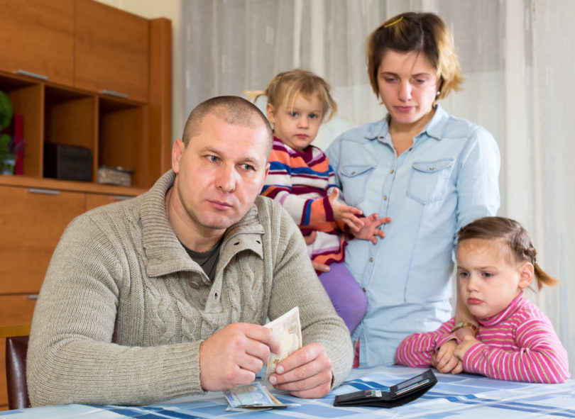 Family having problems with cash. Father is sitting at the table with money in his hands his wife and two sad daughters are sitting behind him