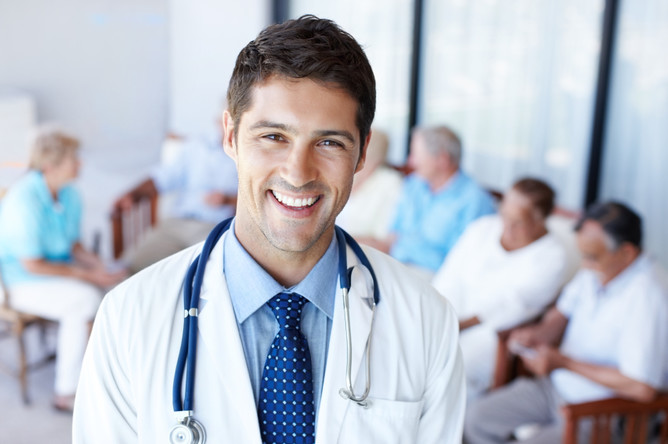 Closeup portrait of a handsome physician with group of senior patients blurred in the background