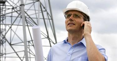 Ingenieur mit Plan telefoniert auf Baustelle